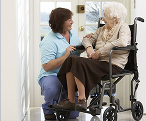 An elderly woman in a wheelchair and kneeling caregiver by the front door
