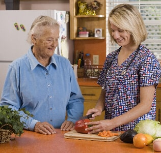 Senior care provider in the kitchen with a senior woman
