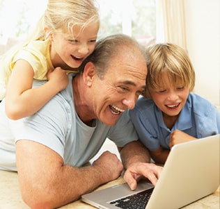 Grandpa with his grandchildren on a laptop