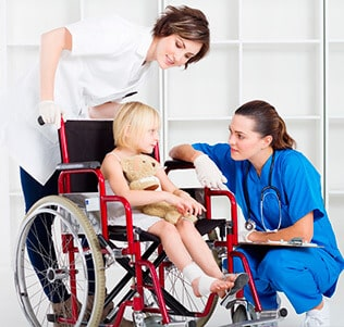 A child in a wheelchair and two nurses